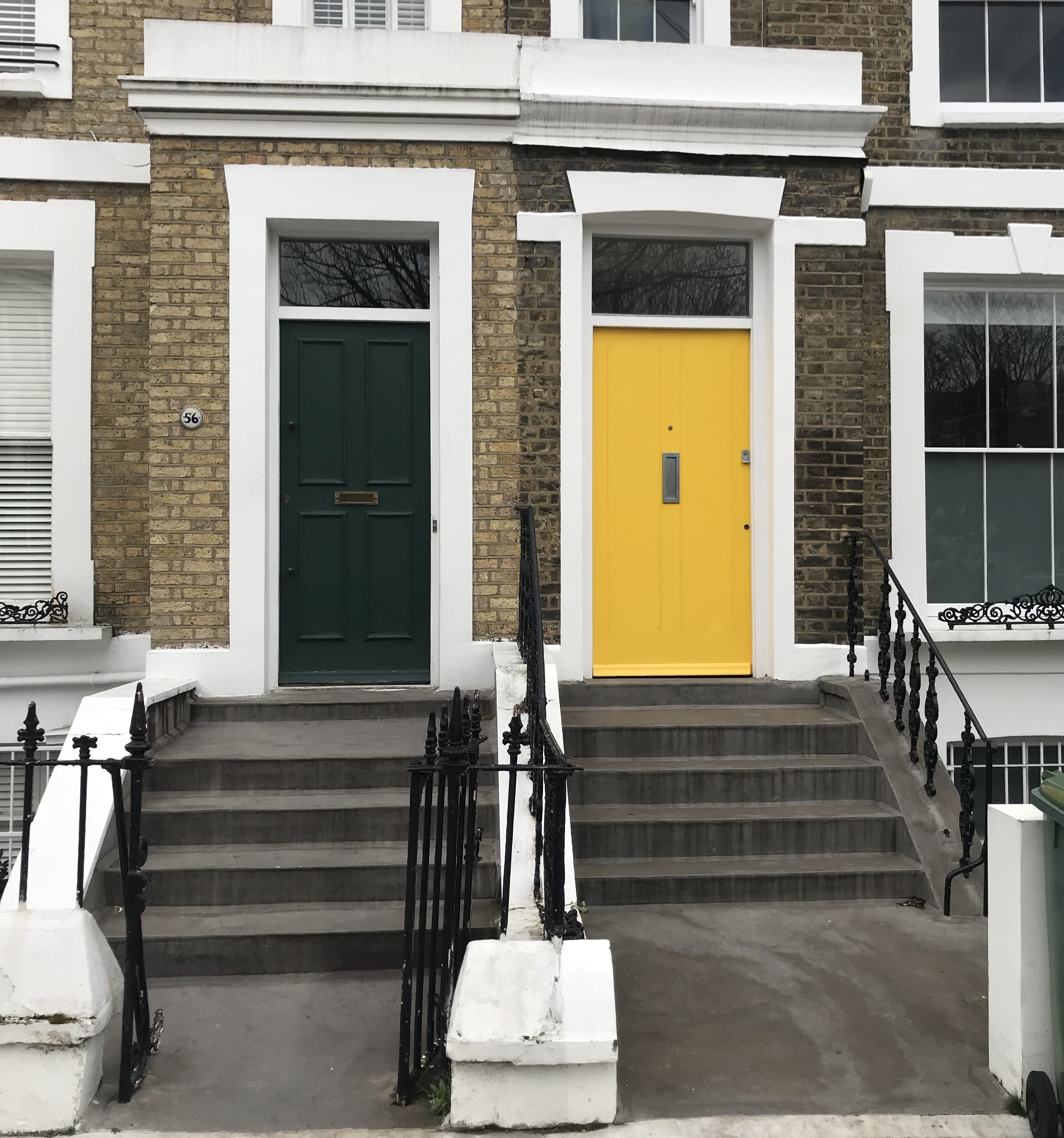 Two townhouses in Camden town London, one with a black door one with a yellow