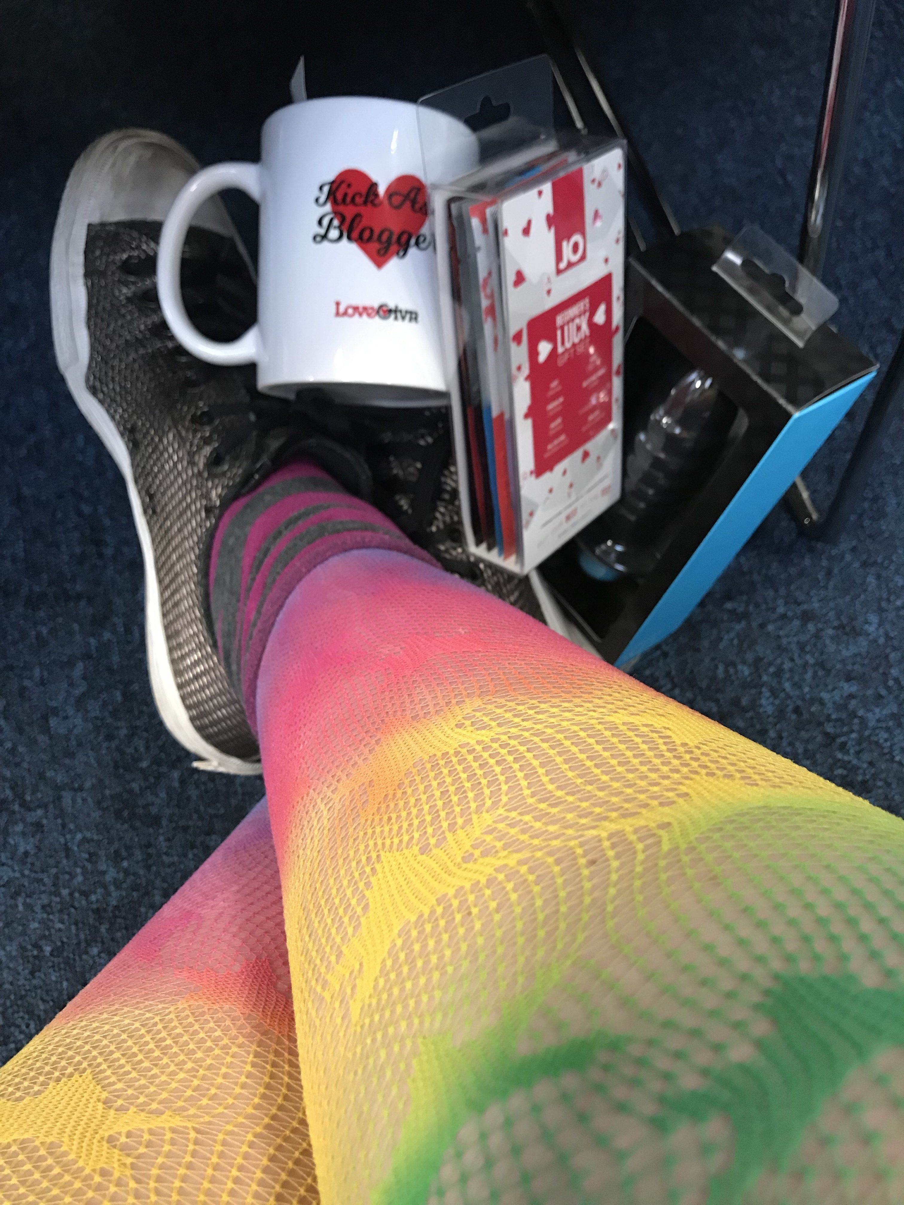 The bottom of my legs with colorful rainbow fishnet tights and converse sneakers. On my feet are a sex bloggers mug, a packet of use samples and a rather large butt plug I won at Eroticon