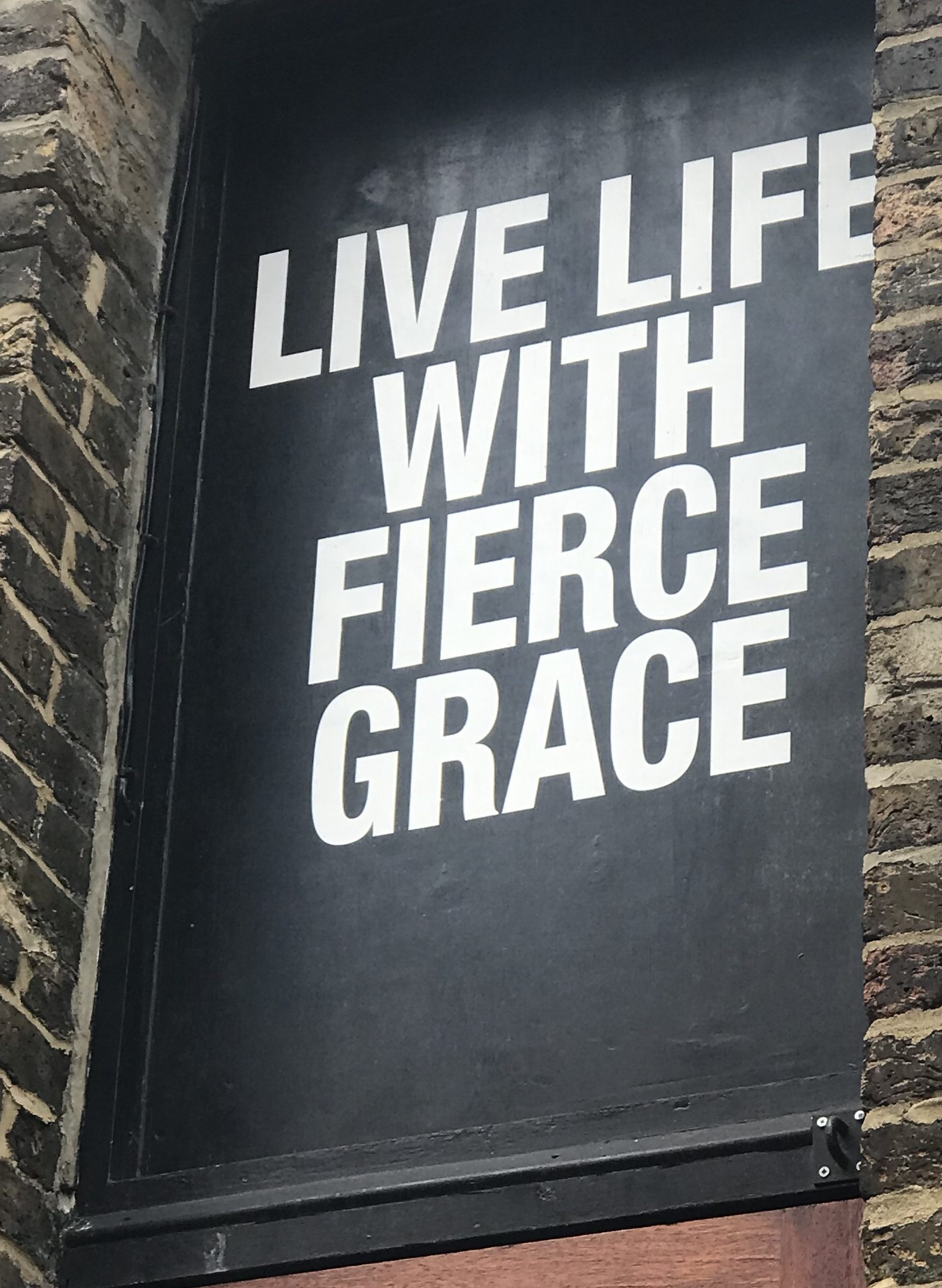 Sign in a yoga studio window that says live life with fierce grace