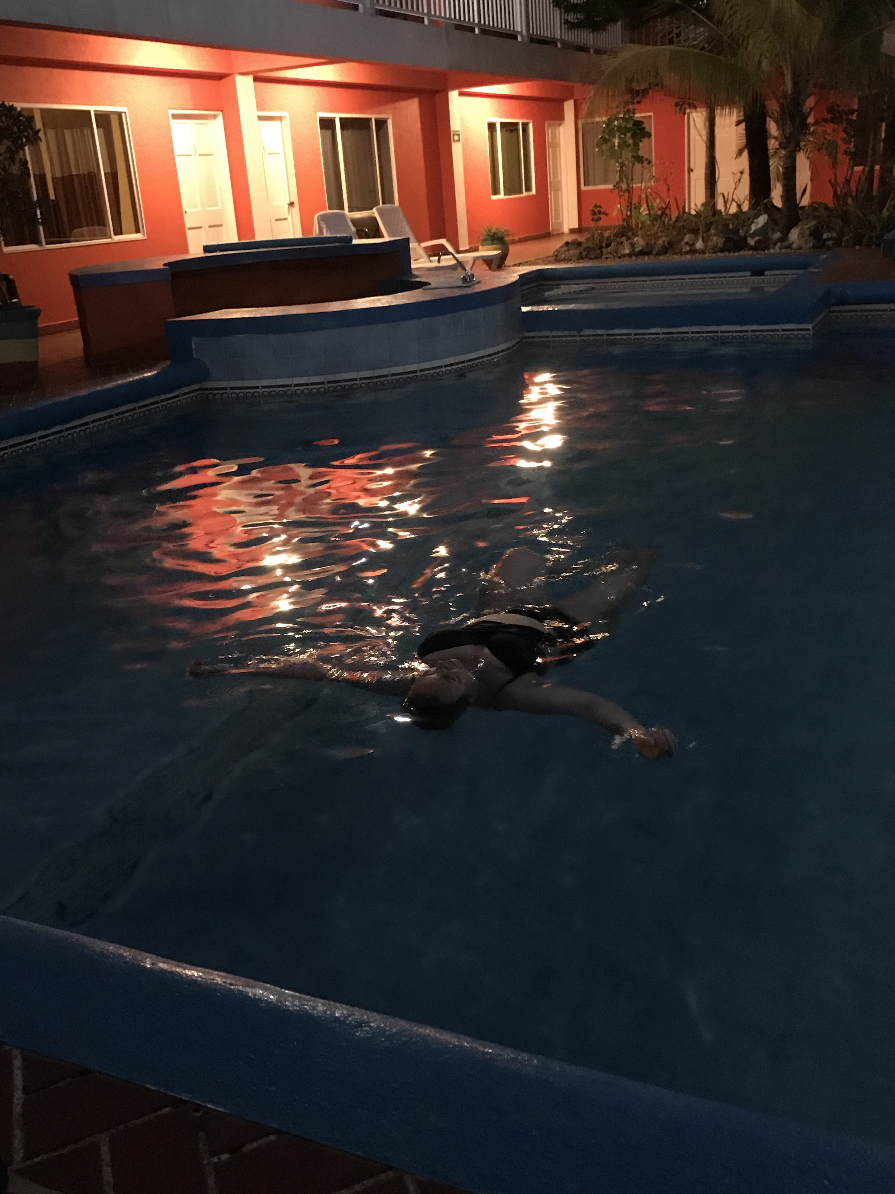Dark night with lights on pool and someone swimming