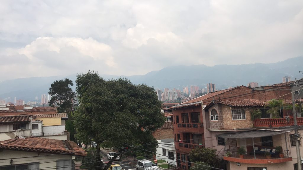 Picture of the hills of Medellin with cloud cover and green mountains as well as local houses