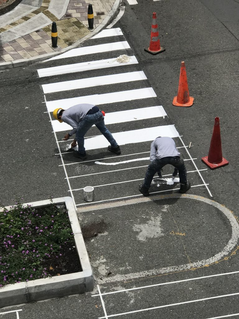 Men working to manually paint lines in the street
