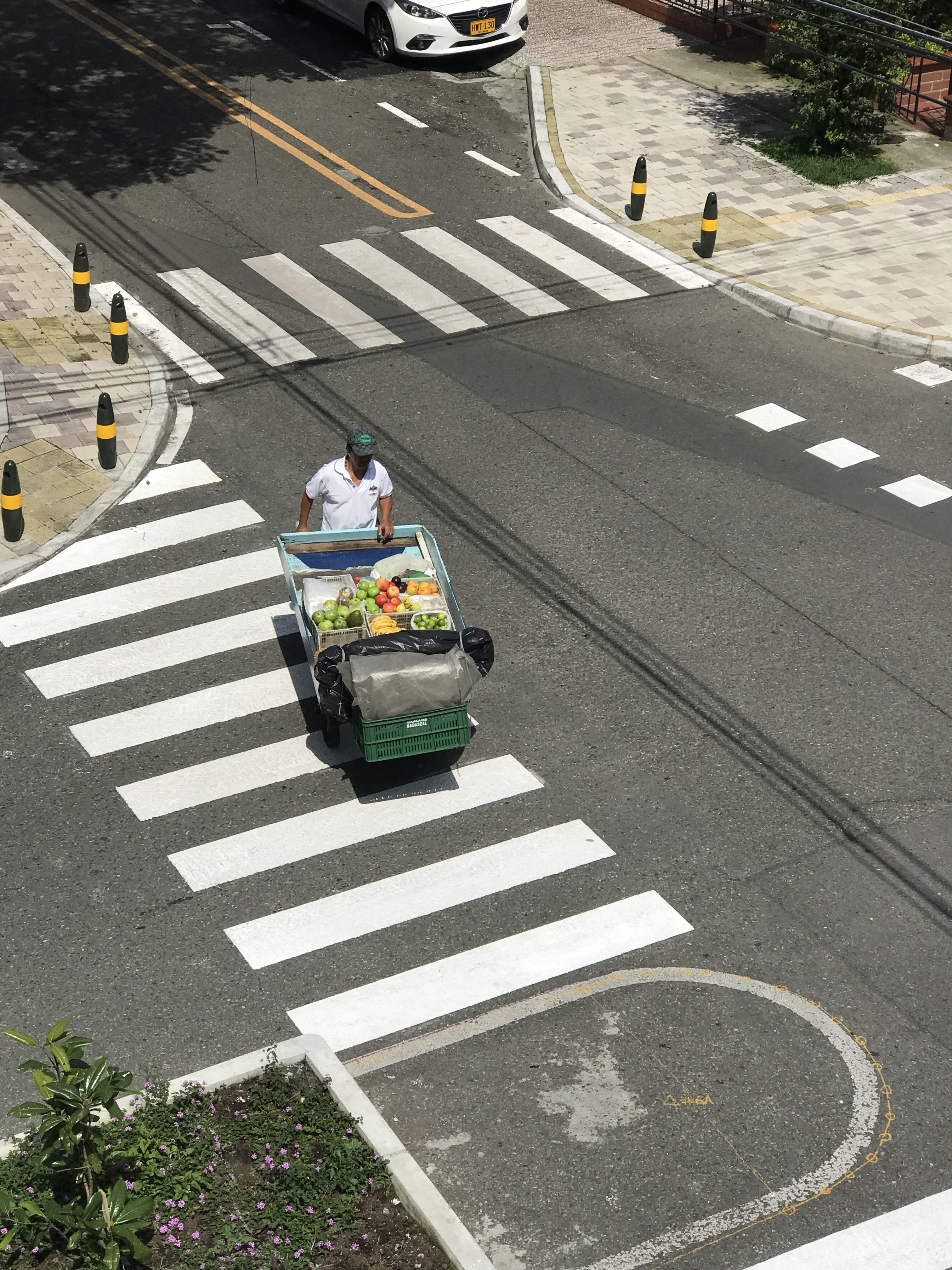 Street vendor walking across white lines selling fresh tropical fruits from a cart