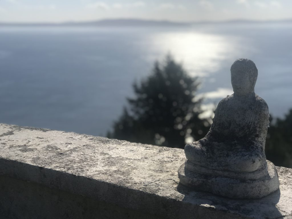 Image of a Buddha statue with the ocean and sunshine blurry behind it