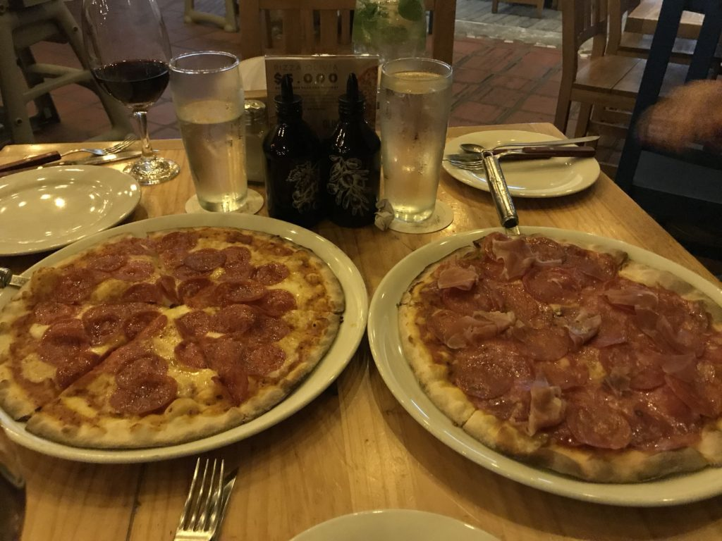 two pizzas with glasses of wine