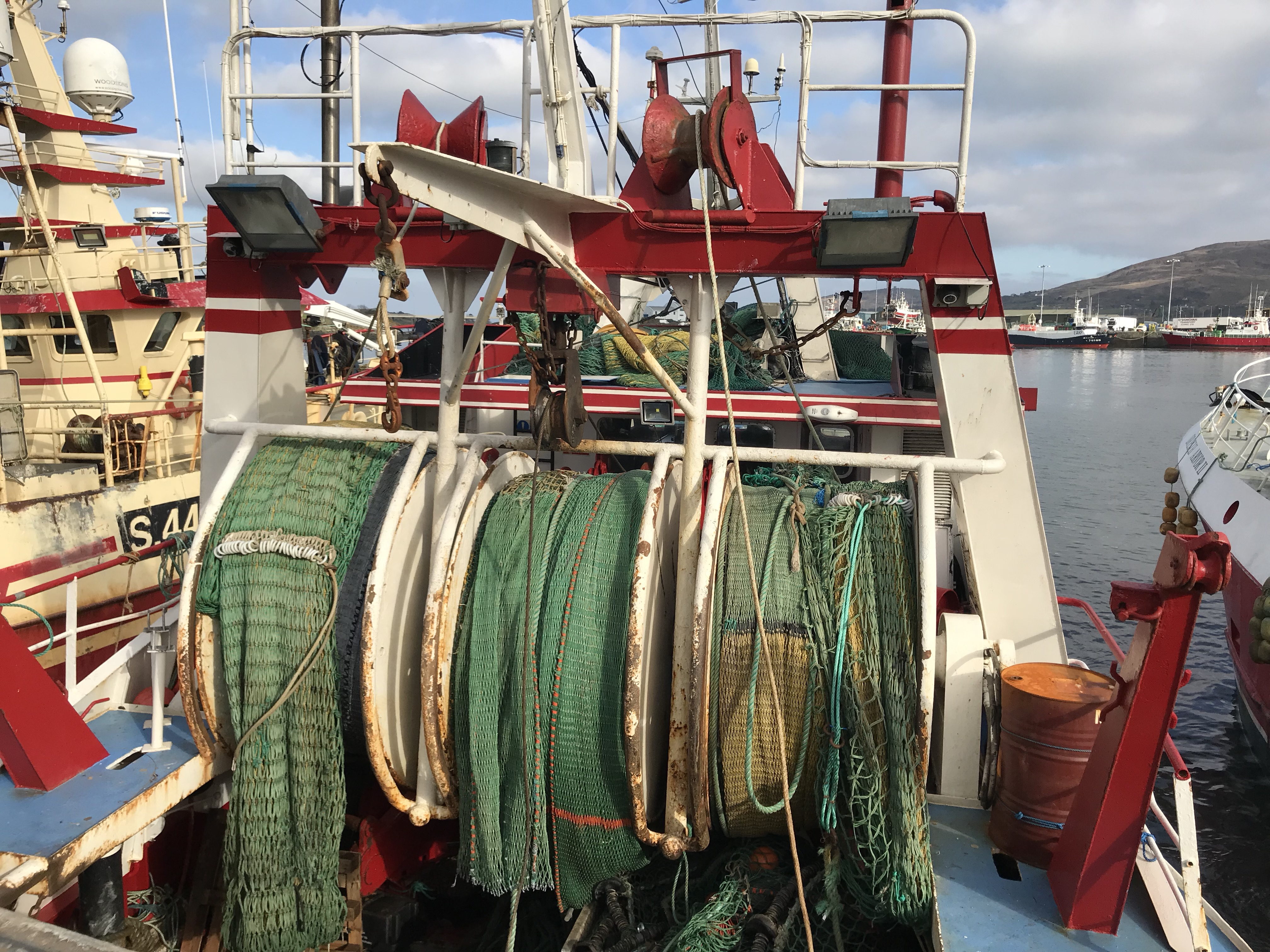Large spools of green fishing net on the back of a fishing boat
