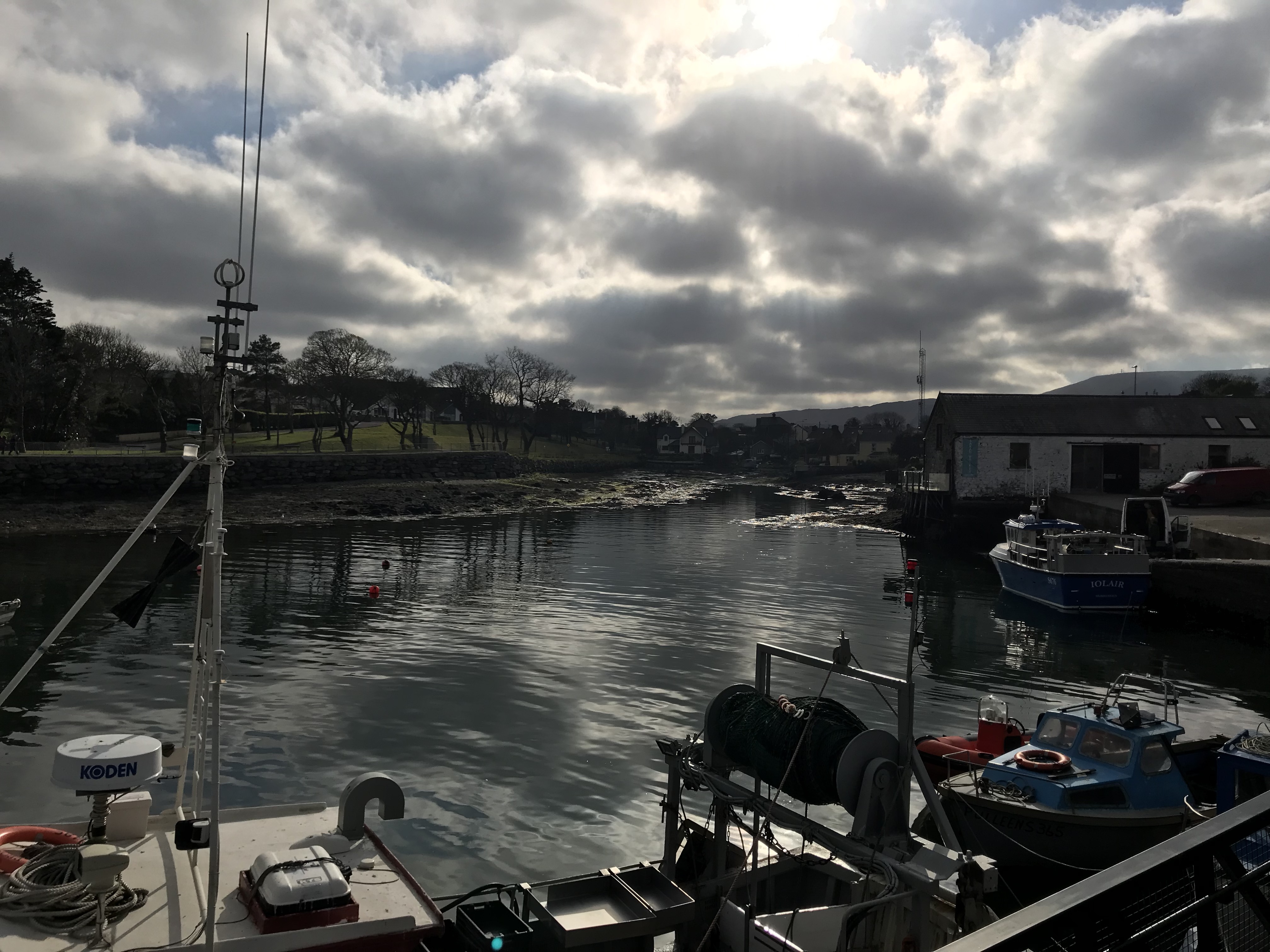 Cloudy brooding sky overlooking a harbor inlet in a small Irish fishing village