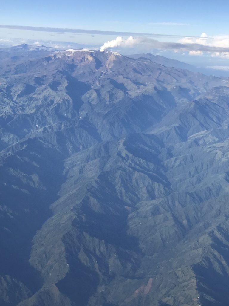 Shot from an airplane of very high green mountains with a column of volcano ash coming from one in the distance