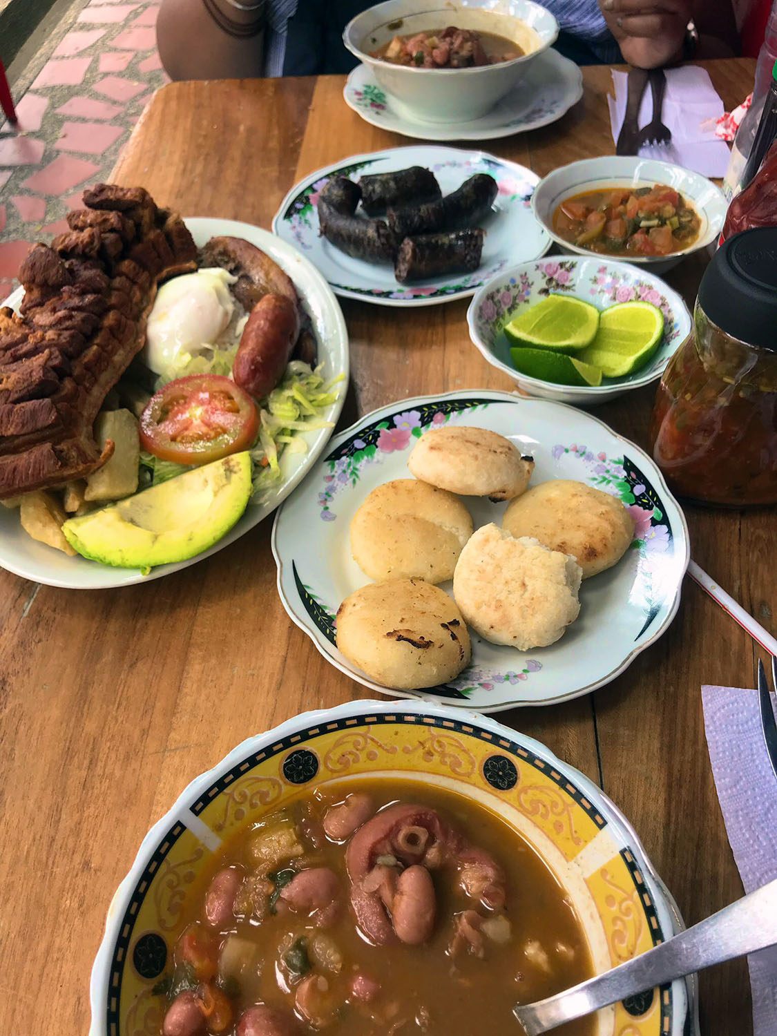 table fully loaded with a local meal called Bandeja Paisa
