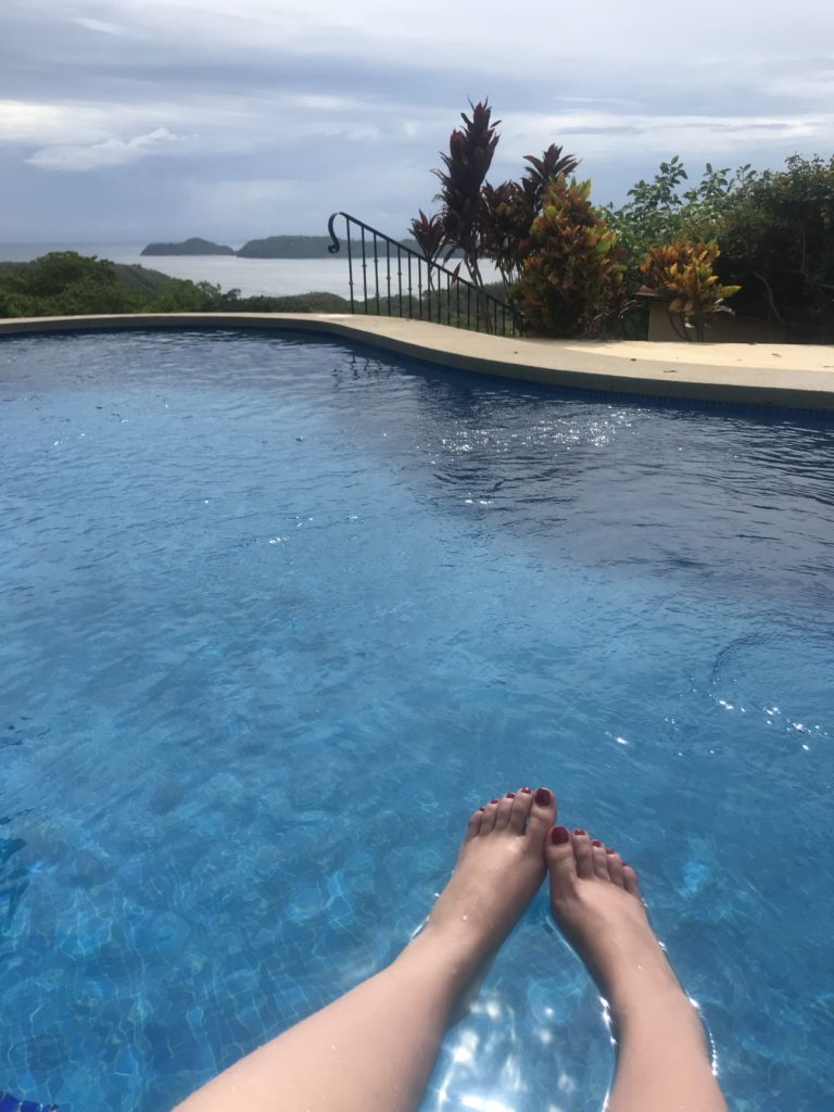 Feet in the pool in the sunshine