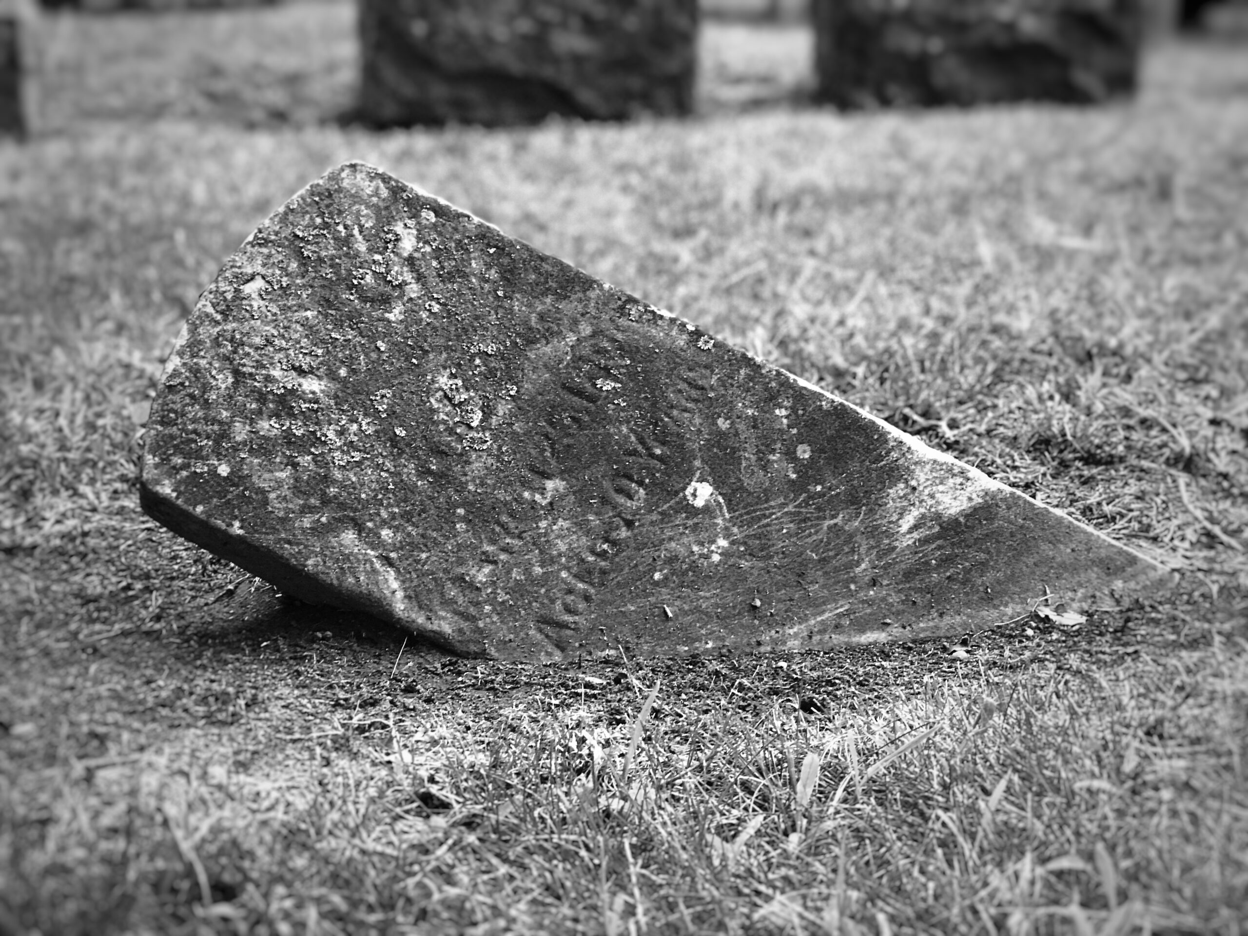 black and white photo of fallen old grave stone